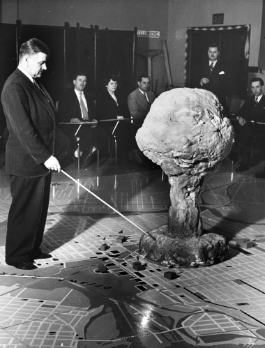 Civil Defence training officer Lt. Col. W. Arthur Croteau points at a model of an atom bomb blast above a map of Ottawa during a 1952 exercise